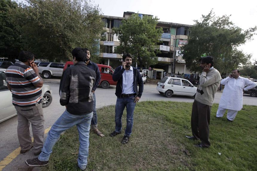 Men stand on a road divider after vacating their office buildings following an earthquake, in Islamabad, Pakistan, on Oct 26, 2015.