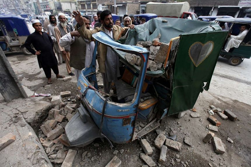 People removing debris from a rickshaw on a road following a 7.7 magnitude earthquake, in Peshawar, Pakistan, on Oct 26, 2015.