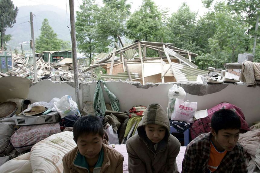 Children huddle together in what was once their home on May 14, 2008, after an 8.0 magnitude earthquake hit China's Sichuan province.
