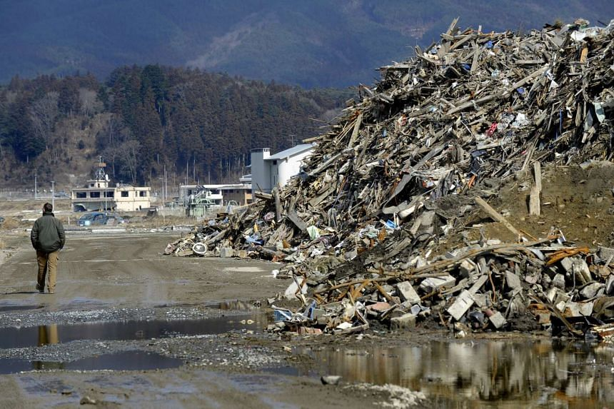 A resident of Rikuzentakata, Iwate Prefecture, walks past a mountain of debris about 5.5m high, as clean up efforts continue more than one year after the 2011 earthquake and tsunami, on Feb 24, 2012.