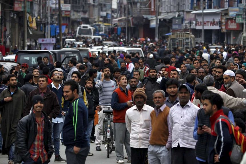 People stand on a road after vacating buildings following an earthquake, in Srinagar on Oct 26, 2015.