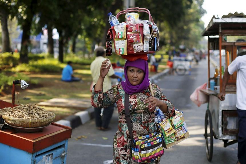 A woman street vendor who sells drinks and food walks on the street in Jakarta Sept 1, 2015.