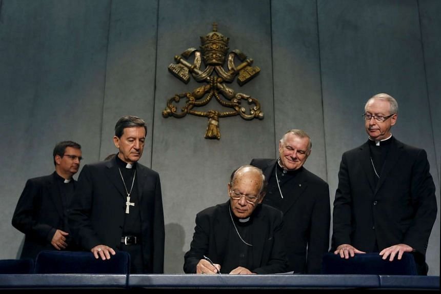 Cardinal Oswald Gracias (centre) signs an appeal to the UN on climate change next to Cardinal Ruben Salazar Gomez (second from left) during a news conference at the Vatican on Monday.