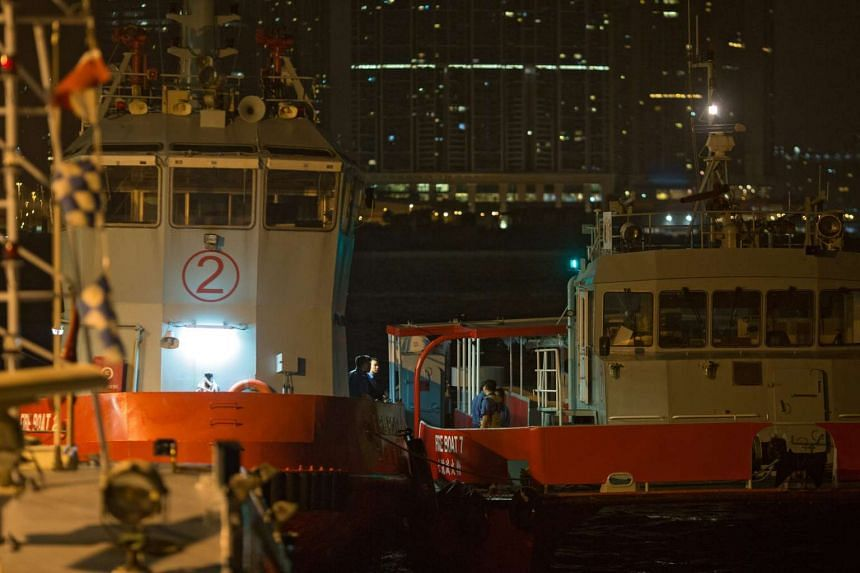 The crew of the Fire Services Department rescue boats wait at Government Pier in Hong Kong early this morning, after more than 100 people were injured on 25 when a high-speed ferry returning from Macau hit an 'unidentified object' south of Lantau Isl
