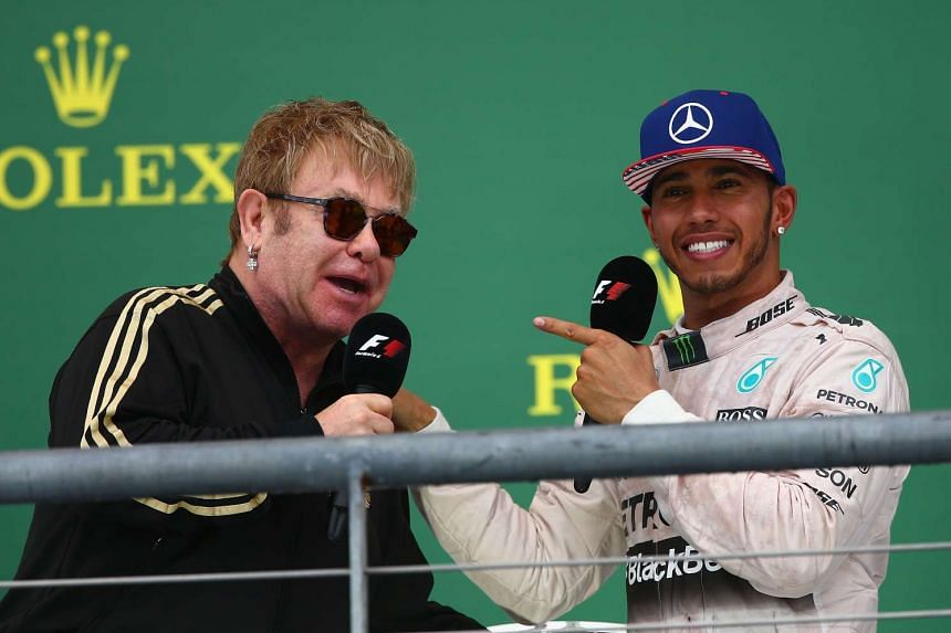 Lewis Hamilton of Great Britain and Mercedes GP celebrates on the podium with Elton John after winning the United States Formula One Grand Prix and the championship in Austin, Texas on Sunday.