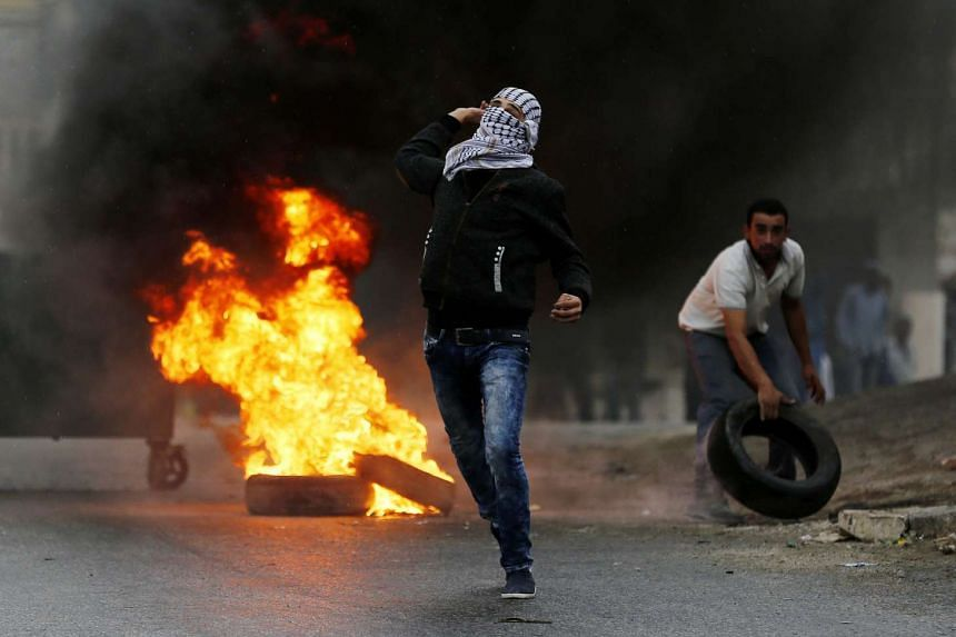 Palestinian protesters throw stones during clashes with Israeli soldiers in the West Bank village of Si'eer, north of Hebron on Sunday.