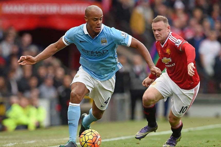Manchester United's English striker Wayne Rooney (right) challenges Manchester City's Belgian defender Vincent Kompany during the EPL match at Old Trafford on Sunday.