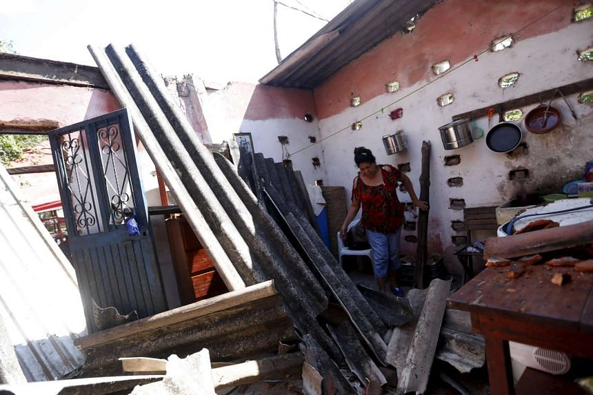 A resident picking her way through the wreckage of her house in Casimiro, Mexico, after Hurricane Patricia struck. The record-breaking hurricane, however, caused relatively little damage and no deaths were reported.