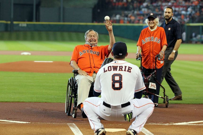 Former president George H. W. Bush throwing out the ceremonial first pitch to Houston Astros third baseman Jed Lowrie as his wife, Mrs Barbara Bush, looks on prior to Game 3 of the American League Division against the Kansas City Royals.
