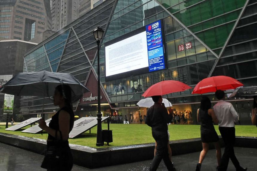 A file picture of pedestrians walking past a digital screen displaying stocks index data at the financial district in Singapore. PHOTO: AFP
