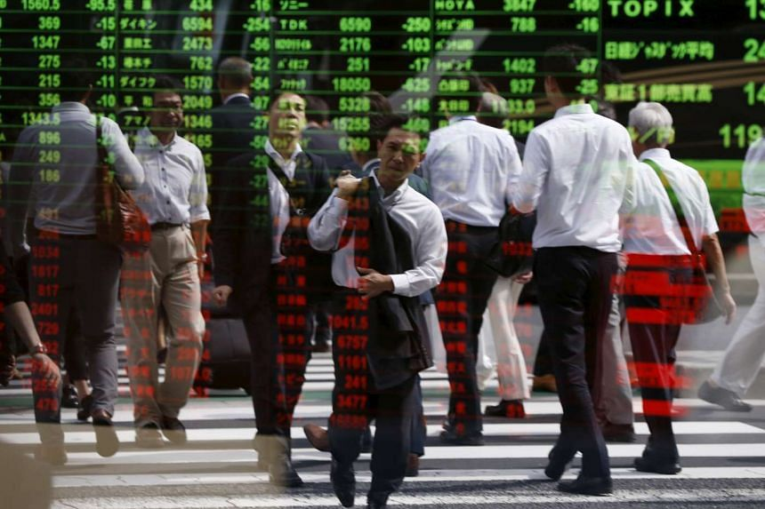 Passers-by reflected on a stock quotation board at a brokerage in Tokyo on Sept 29, 2015.