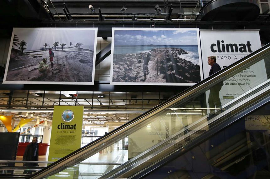"""A man passes by photographs part of the exhibition entitled """"climat l'expo a 360°."""" It is the first exhibition since the reopening of the Cite des Sciences et de l'Industrie (Science and Industry museum) in Paris on Oct 12, 2015, ahead of the Clim"""