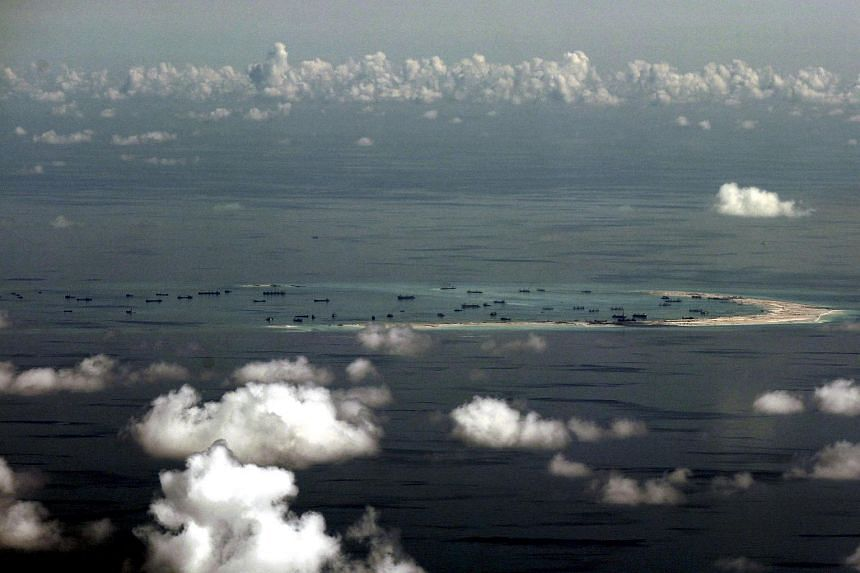 An aerial photograph taken though a glass window of a Philippine military plane shows the alleged on-going land reclamation by China in the South China Sea.