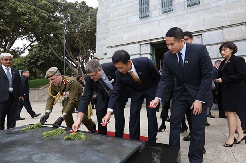 Acting Minister Ong Ye Kung (second from right) and Parliament Secretary Amrin Amin (far right) place poppies on the Tomb of the Warrior as acts of remembrance of New Zealand servicemen and women who lost their lives in times of war.