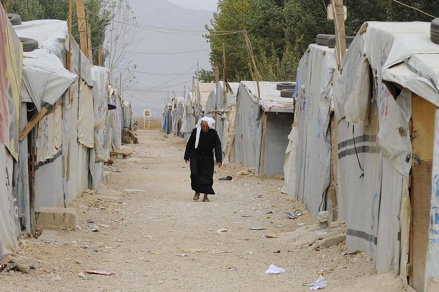 A Syrian refugee man walks past tents at a makeshift settlement in Bar Elias in Lebanon's Bekaa Valley, on Oct 23, 2015.