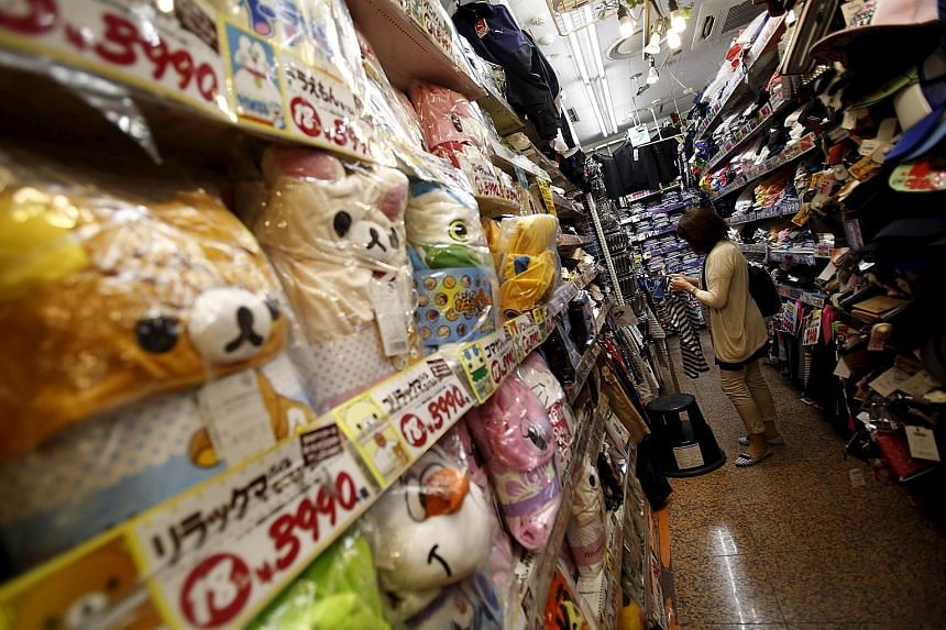 A shopper at a discount store in a Tokyo shopping district. The Bank of Japan's aggressive intervention has been central to Premier Shinzo Abe's economic policies, but events have conspired to blunt its impact, such as the sales tax increase last yea