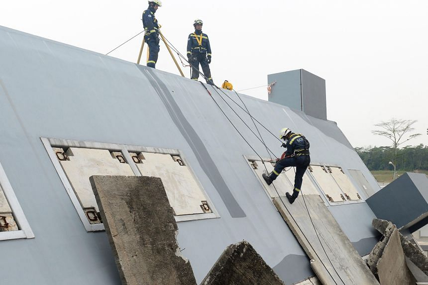 At the new training centre, officers can rappel down the side of a collapsed building (far left), and do confidence jumps into a 9m-deep pool (left). Special Operations Command officers practising a simulated attack at the new drive-in shooting range