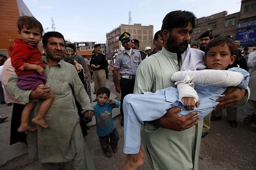 Injured children being carried to a hospital in Peshawar, Pakistan, yesterday. Afghanistan's strongest earthquake in more than six decades was 213km deep and centred 254km north-east of Kabul in Badakhshan province. The US Geological Survey measured