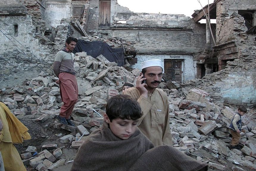 Residents making their way past the rubble of a house in Mingora in Swat district, Pakistan, after it was damaged by an earthquake yesterday. The 7.5-magnitude quake struck Afghanistan's Hindu Kush region and was felt throughout much of South Asia, k