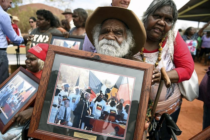 Mr Reggie Uluru displays a photograph of himself at the original handover in 1985