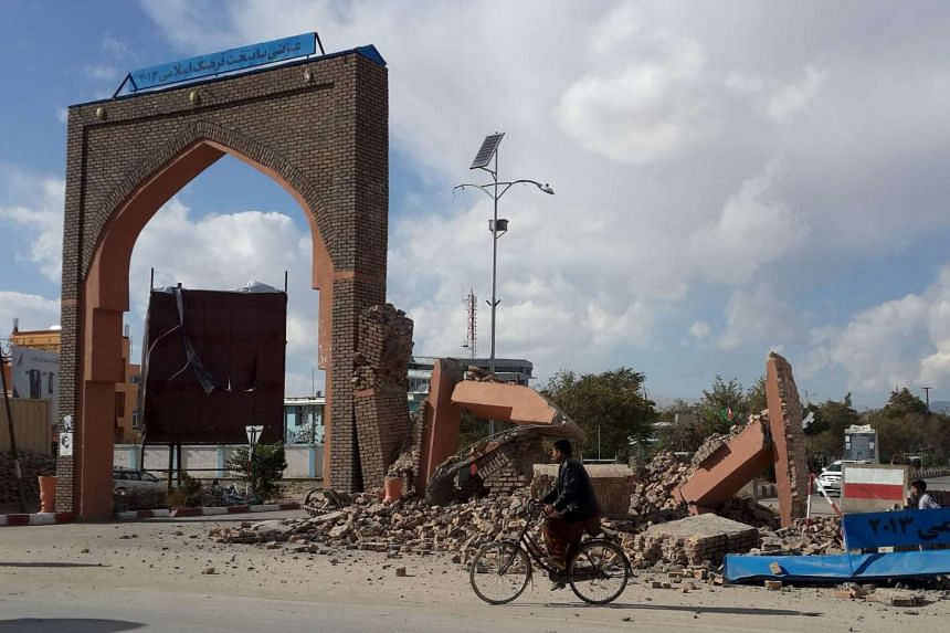 A man rides his bicycle next to buildings damaged by the earthquake in Ghazni, Afghanistan, on Oct 26, 2015.