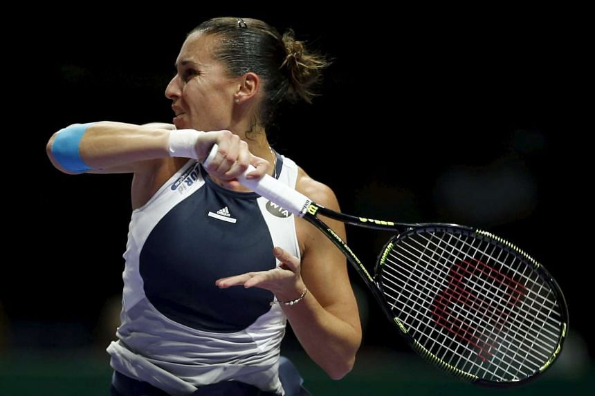 Flavia Pennetta of Italy hits a return to Agnieszka Radswanka of Poland during their women's singles tennis match at the WTA Finals at the Singapore Indoor Stadium on Oct 27, 2015.