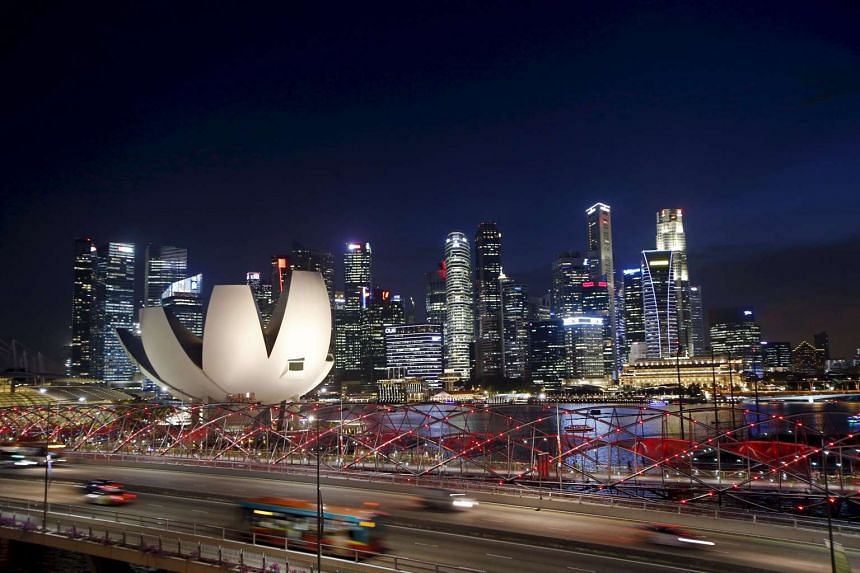 Vehicles travel on a bridge past the skyline of the central business district in Singapore.
