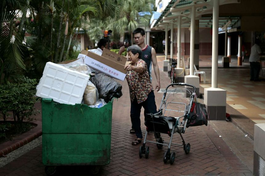 An elderly rag and bone woman picking up a cardboard box outside Geylang Bahru food centre.