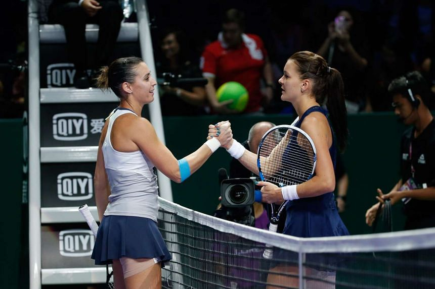 Italy's Flavia Pennetta (left) shaking hands with Poland's Agnieszka Radwanska after defeating her 7-6(5), 6-4 at the WTA Finals at the Singapore Indoor Stadium on Oct 27, 2015.