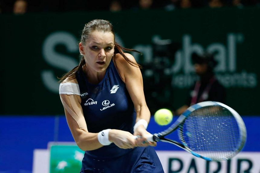 Poland's Agnieszka Radswanka hits a backhand shot to Flavia Pennetta of Italy during their WTA Finals match at the Singapore Indoor Stadium on Oct 27, 2015.