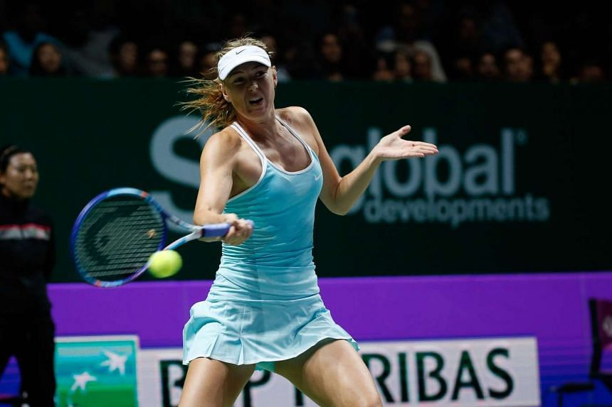 Russia's Maria Sharapova hitting a return to top seed Simona Halep of Romania during their WTA Finals match at the Singapore Indoor Stadium on Oct 27, 2015.