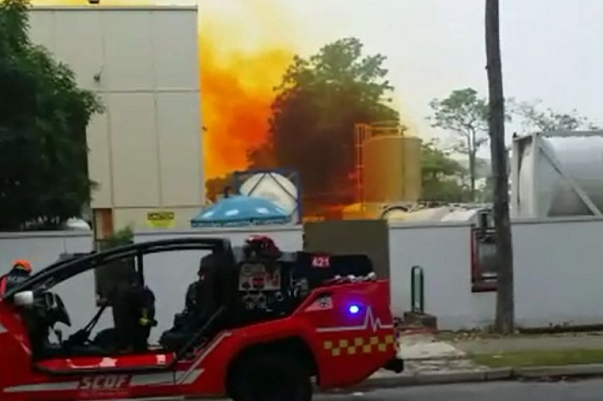Photo of the orange smoke coming from a management plant in Tuas, and of SCDF using water jets on the smoke.