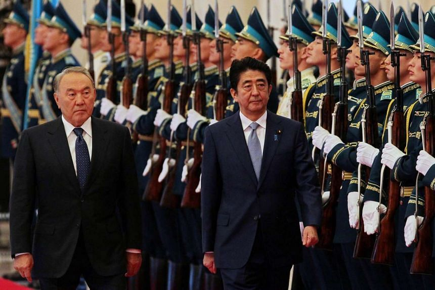Kazakh President Nursultan Nazarbayev (left) and Japanese Prime Minister Shinzo Abe reviewing an honour guard during a welcoming ceremony in Astana, Kazakhstan, on Oct 27, 2015.