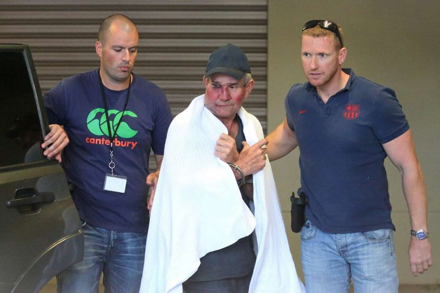 Wanted fugitive Gino Stocco (centre) is escorted by two policemen as he is taken into Dubbo police station after he and his son Mark were arrested in Dunedoo, New South Wales, on Oct 28, 2015.