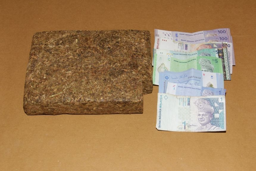 A 1kg block of cannabis and cash that was confiscated from a 35-year-old Malaysian in Woodlands by the Central Narcotics Bureau.