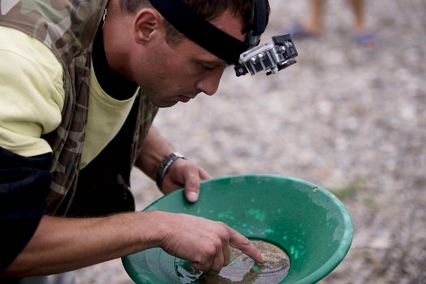 A man pointing to alluvial gold in a pan of sand from the Tundzha river near Kazanlak, central Bulgaria, on Aug 22, 2015.