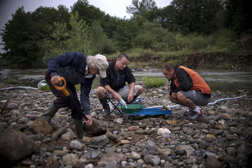 Men rinsing sand as they mine for alluvial gold in the Tundzha river near Kazanlak, central Bulgaria, on Aug 22, 2015.