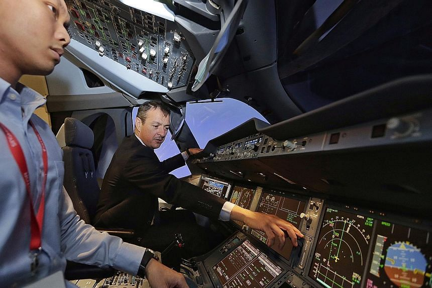 Capt Lardet giving a tour of the A350 flight simulator to the media at the Airbus Asia Training Centre (AATC), located in the SIA Training Centre, yesterday. The AATC will move to its own premises in Seletar next year.