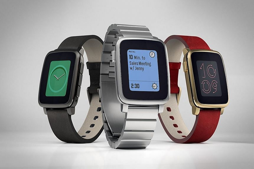 The Pebble Time Steel smartwatch comes in (from left) gunmetal, stainless steel and gold with a red strap.