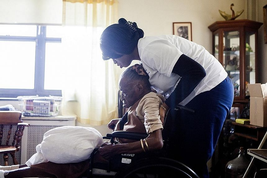Home health aide Alicia Joseph helps dementia patient Naomi Wallace at her New York home. End-of-life costs for dementia are more expensive than for heart disease or cancer.