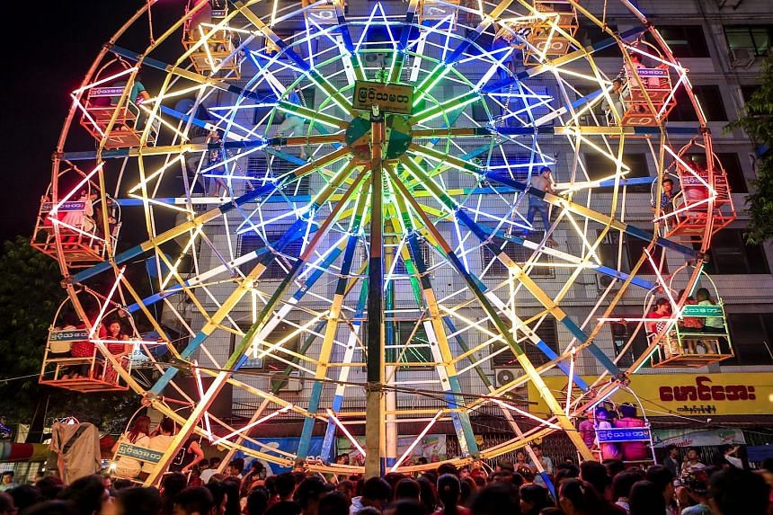Revellers enjoying a ride on a human-powered ferris wheel during the Thadingyut Festival, or Festival of Lights, in Yangon, Myanmar, on Monday. Gutsy ferris wheel workers spread out across the mammoth structure, as they manually turned the wheel with