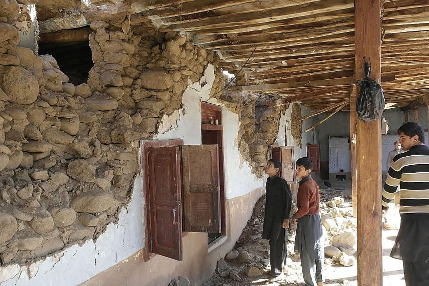 Residents surveying their damaged homes yesterday in Lower Dir, Pakistan, a day after the massive quake.