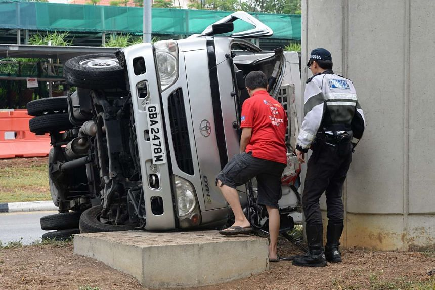 A lorry hit an MRT track pillar and overturned along New Upper Changi Road near Tanah Merah MRT station, outside Katong Flower Shop, on Oct 28, 2015.