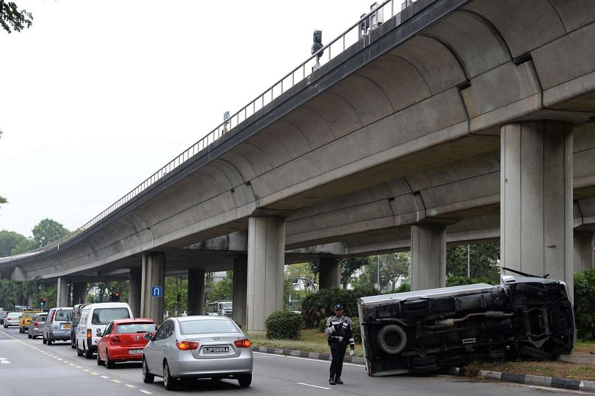 A traffic police officer helping to direct traffic around a truck that overturned near Tanah Merah MRT station on Oct 28, 2015.