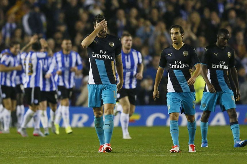 Arsenal's Olivier Giroud (left) and Mathieu Flamini look dejected after Sheffield Wednesday's third goal.