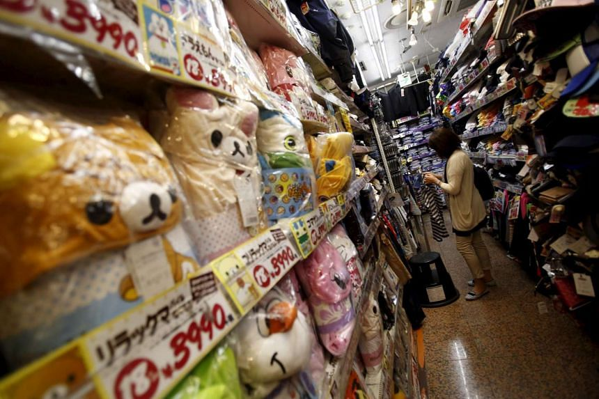 A shopper looks at items inside a discount store at a shopping district in Tokyo, Japan, Jul 29, 2015.