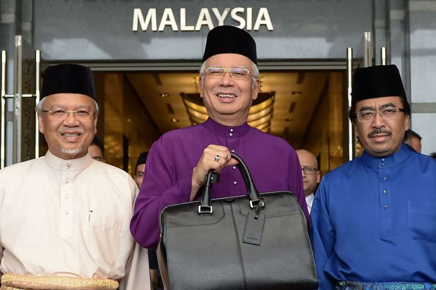 Malaysia's Prime Minister Najib Razak (centre) holding a briefcase as he poses for photos with second Finance Minister Ahmad Husni Hanadzlah (left) and Deputy Finance Minister Johari Abdul Ghani (right) before unveiling Malaysia's 2016 budget on Oct