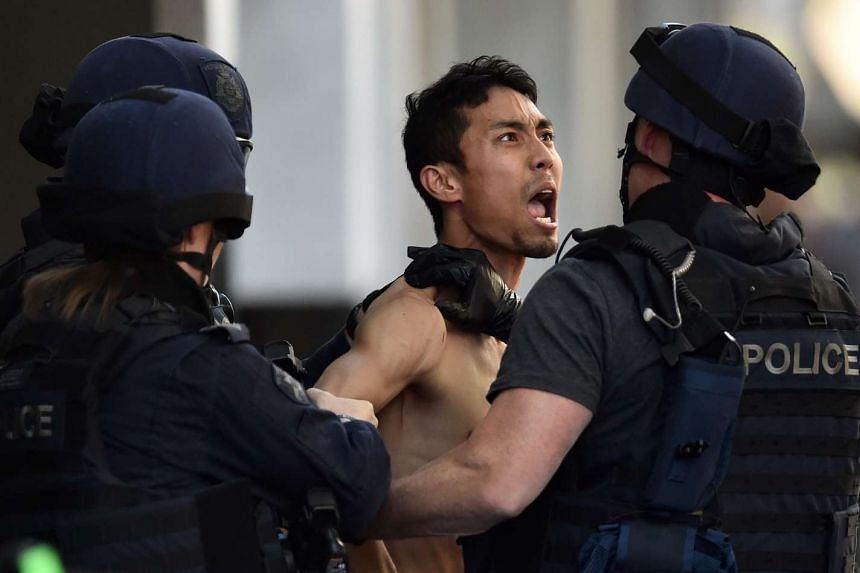 "A Malaysian man who called himself the ""Messiah"" (centre) is detained by special forces outside the Little Ipoh Restaurant in central Melbourne on Oct 27, 2015."