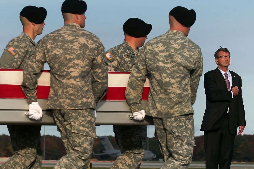 US Secretary of Defence Ash Carter stands at attention while a US Army carry team moves the body of US Army Master Sgt. Joshua L Wheeler - killed in Iraq in a raid on ISIS - at Dover Air Force Base on Saturday in Delaware.