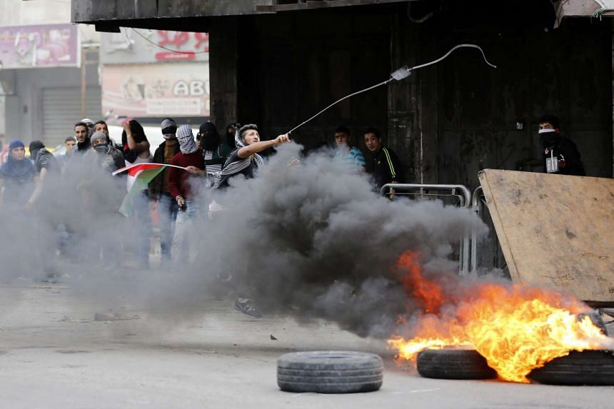 Palestinian protesters throw stones at Israeli soldiers during clashes in the West Bank of Hebron on Tuesday.